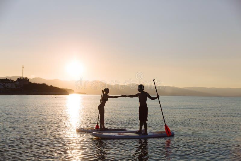 一口海浪的男性剪影和女性在海洋合作手 概念生活方式,体育,爱 库存图片