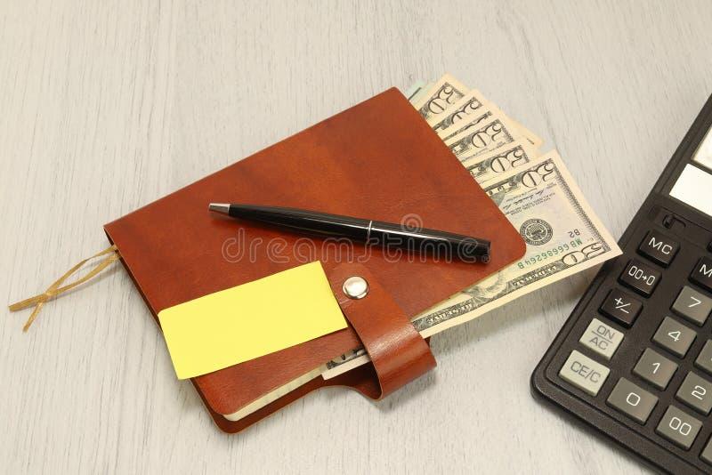 一句棕色皮革笔记本和黑笔谎言在办公桌上 现金美元 标志和便条纸 免版税库存图片