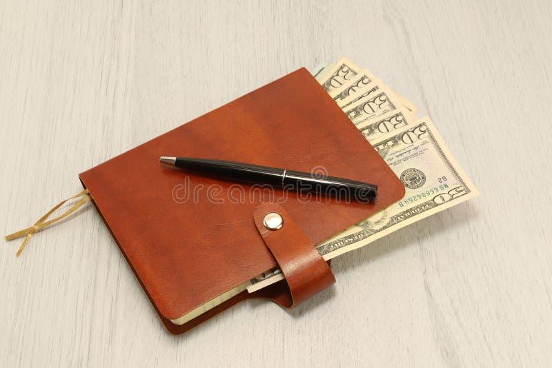 一句棕色皮革笔记本和黑笔谎言在办公桌上 现金美元 免版税图库摄影