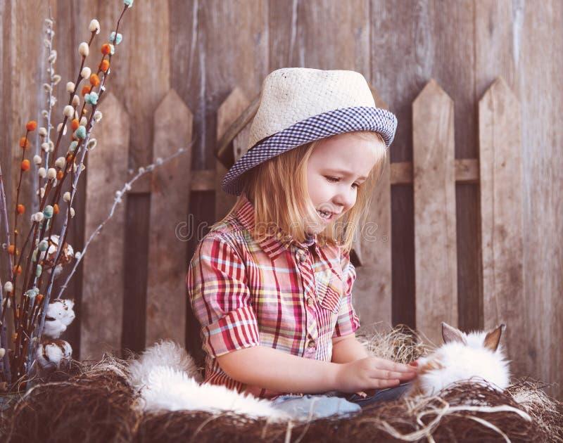一只可爱的女婴和小的白色兔子的画象在t附近 免版税库存图片