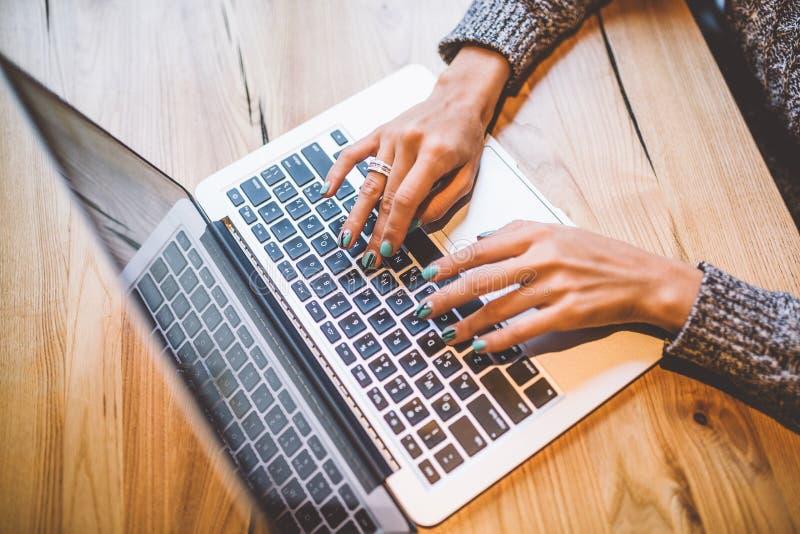 一只女孩` s手的特写镜头在灰色毛线衣用途膝上型计算机技术在咖啡馆的一张木桌上 在手机和gl附近 免版税库存照片