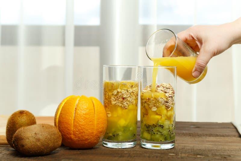 一只女性手倒橙汁入与果子片断的一块玻璃  水平的图象 库存照片