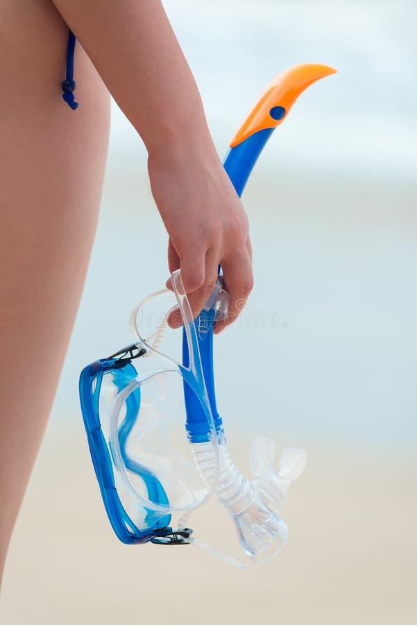 一只女性手拿着一个潜航的面具 免版税图库摄影