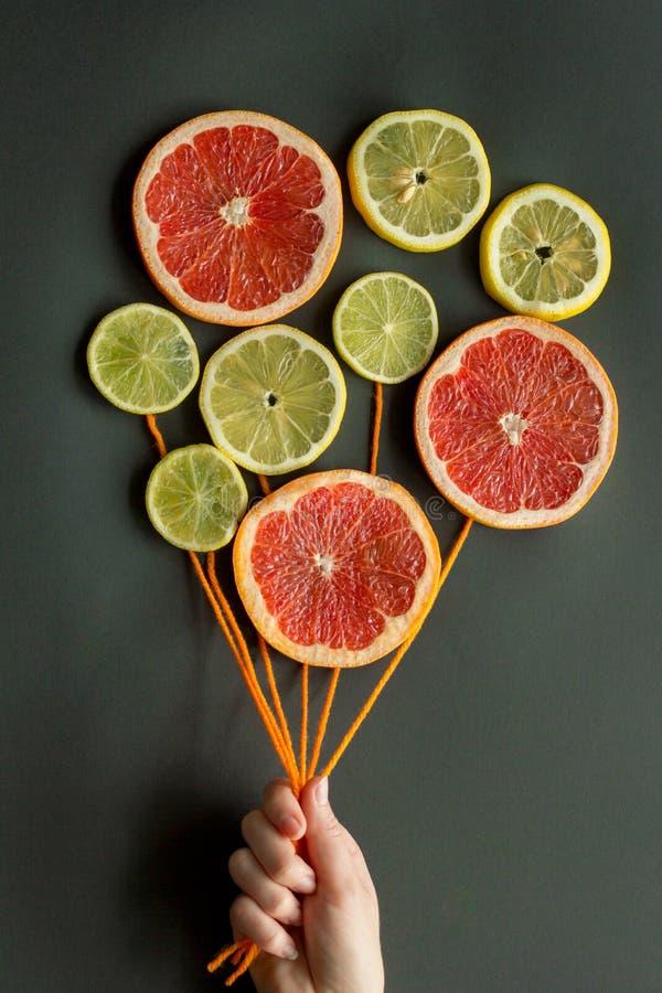一只女性手拿着有橙色螺纹的气球由柑橘切片柠檬,石灰,桔子,在黑背景的葡萄柚做成 免版税库存图片