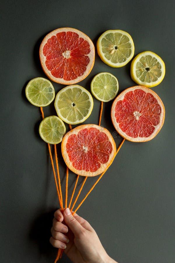一只女性手拿着有橙色螺纹的气球由柑橘切片柠檬,石灰,桔子,在黑背景的葡萄柚做成 免版税库存照片
