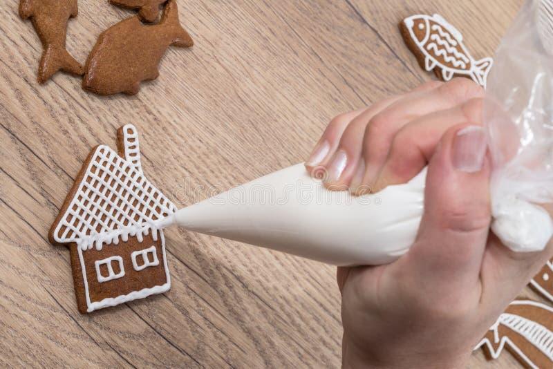 一只女性手的特写镜头,当装饰在木桌上时的圣诞节姜饼 免版税图库摄影
