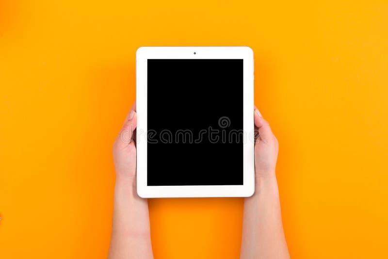 一只妇女手的顶视图使用电话的在橙色背景 免版税库存照片