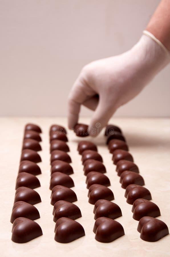 一只手套的手被预定的心形的巧克力 免版税图库摄影