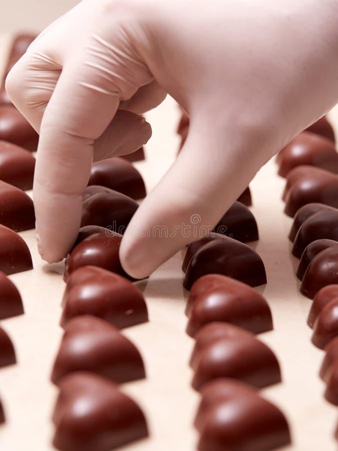 一只手套的手被预定的心形的巧克力 免版税库存照片