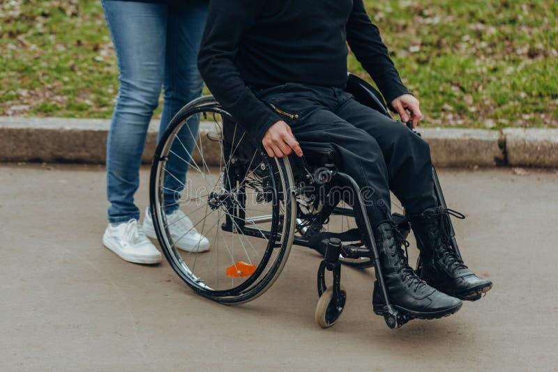一只男性手的特写镜头在一个轮椅的轮子的在步行期间的在公园 一起步行在公园 免版税库存照片