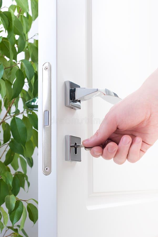 一只男性手的门锁特写镜头有钥匙的 免版税图库摄影