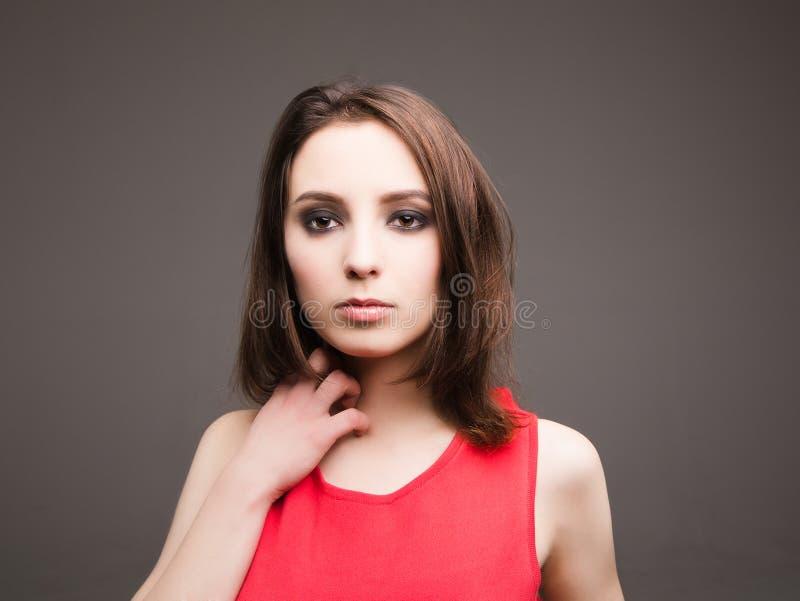 一只红色礼服和发烟性眼睛的典雅的女孩 免版税库存照片