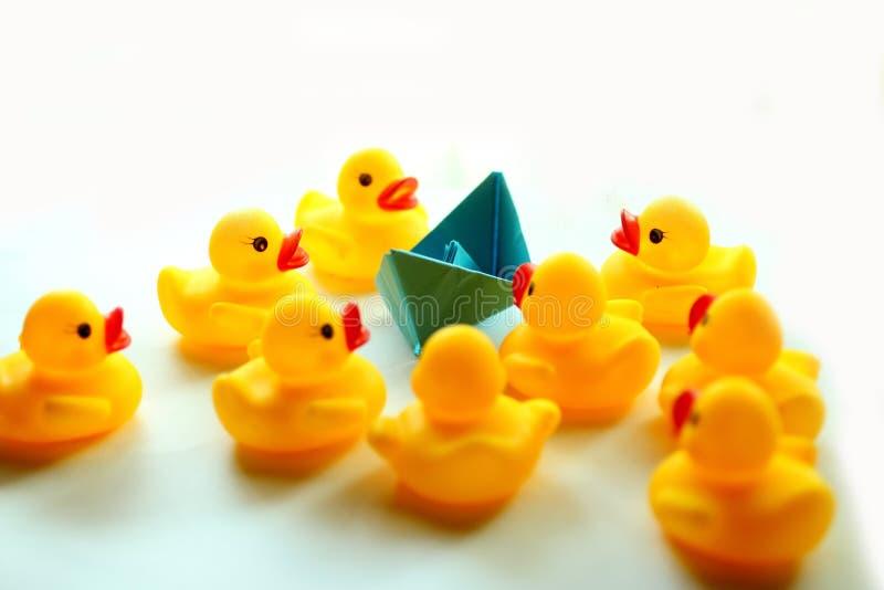 一只蓝色小船纸和黄色橡胶鸭子 库存照片
