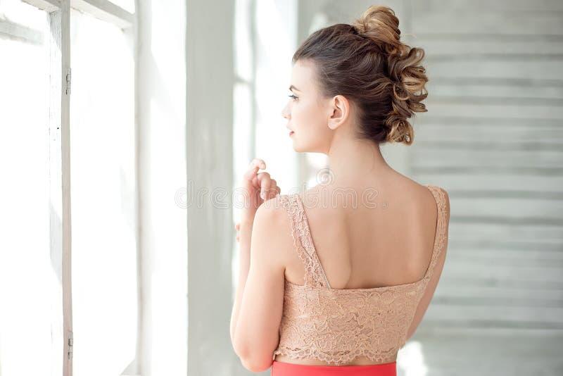一可爱的少女站立与她的在红色裙子和上部围腰的后面在一个大窗口里在一间明亮的屋子 库存照片
