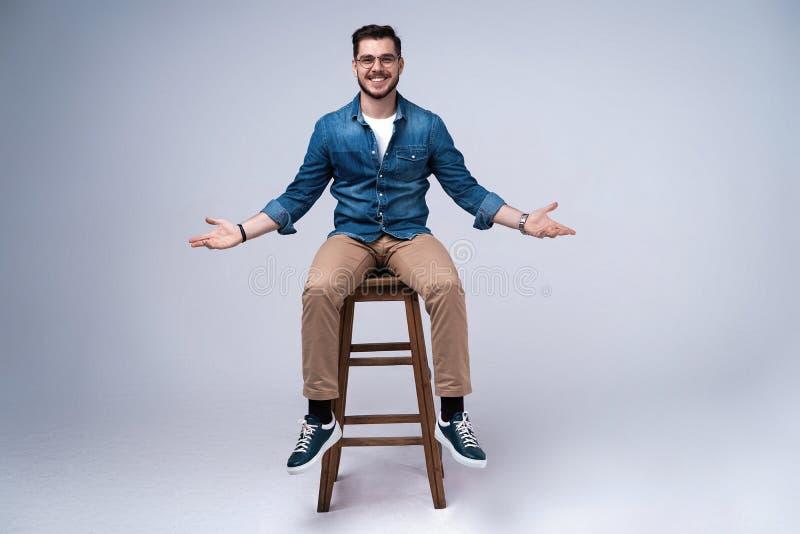 一可爱的年轻人的全长画象牛仔裤衬衣的坐在灰色背景的椅子 免版税库存照片