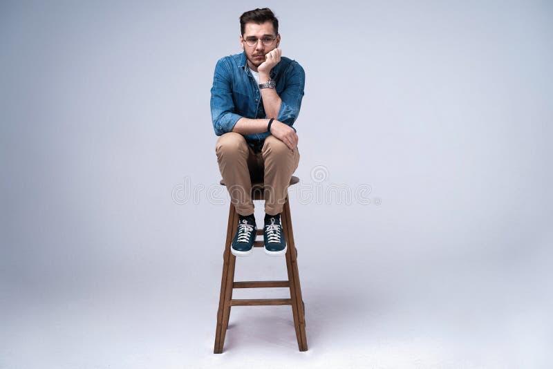 一可爱的年轻人的全长画象牛仔裤衬衣的坐在灰色背景的椅子 图库摄影