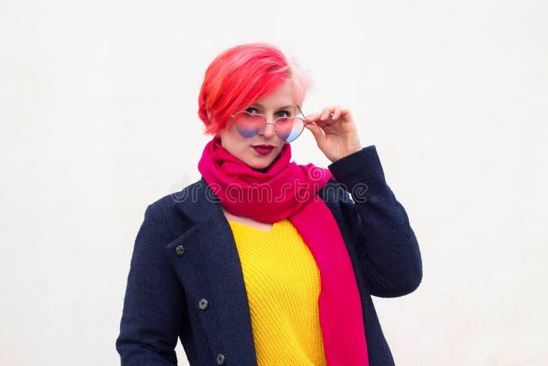 一可爱的年轻女人的画象有色的头发和五颜六色的衣裳的在轻的背景,以心脏的形式玻璃 免版税库存图片