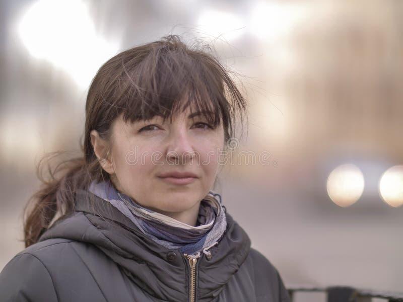 一可爱的年轻女人的画象街道的背景的 免版税图库摄影