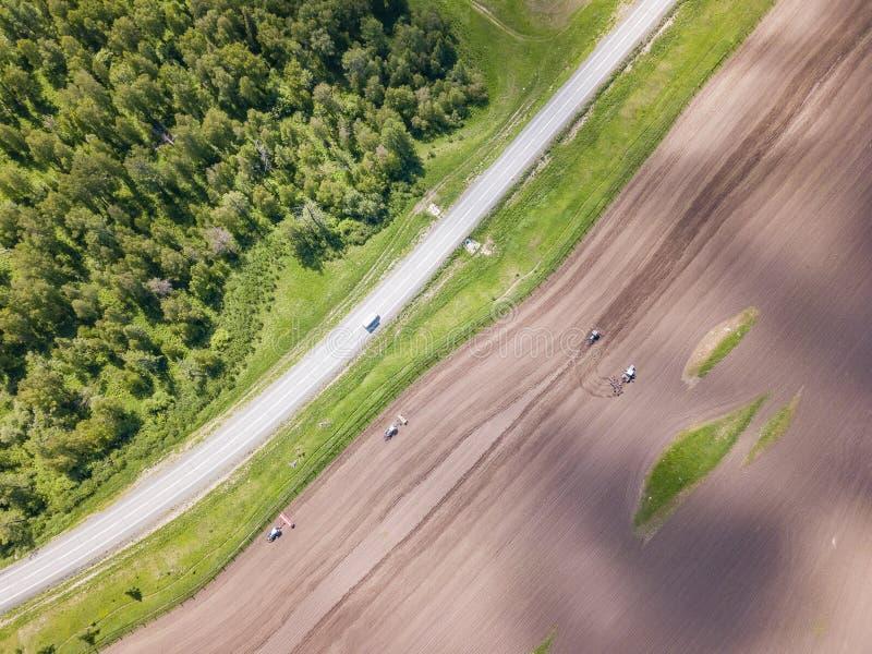 一台农用拖拉机的鸟瞰图在一个领域的在犁增长的食物、蔬菜和水果的土地期间在绿色树附近与 库存图片