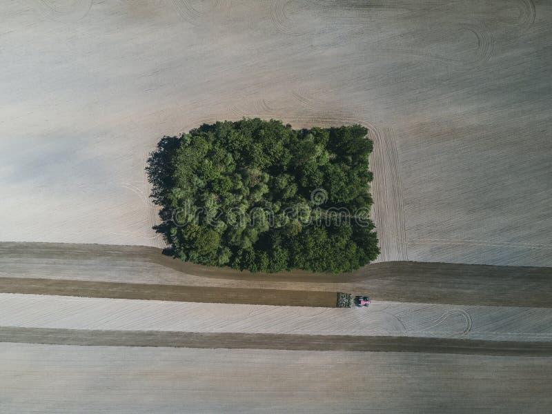 一台农用拖拉机的鸟瞰图在一个领域的在犁增长的食物的土地期间 库存图片