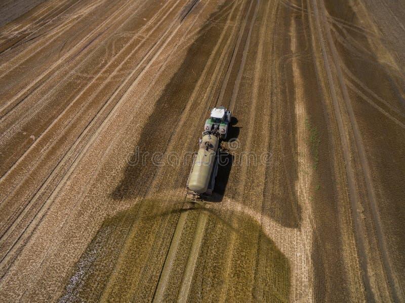 一台农用拖拉机的鸟瞰图有拖车的施肥与肥料的一个新近地被犁的agriculural领域 免版税库存照片