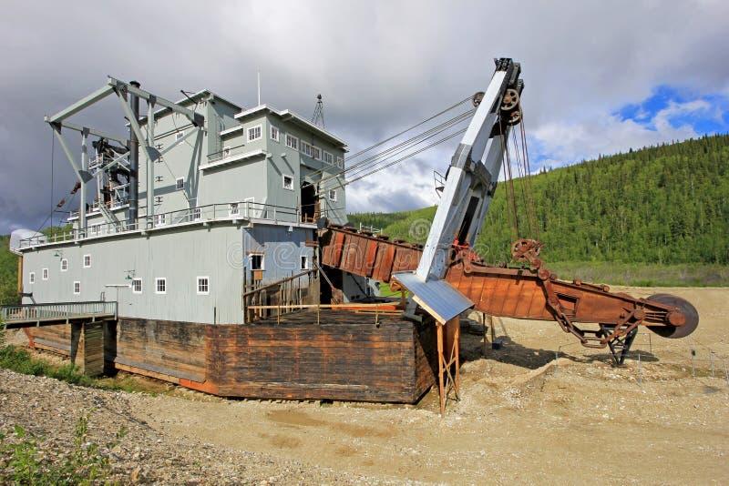 一台历史delelict金挖泥机的遗骸在富矿小河的在道森市,加拿大附近 图库摄影