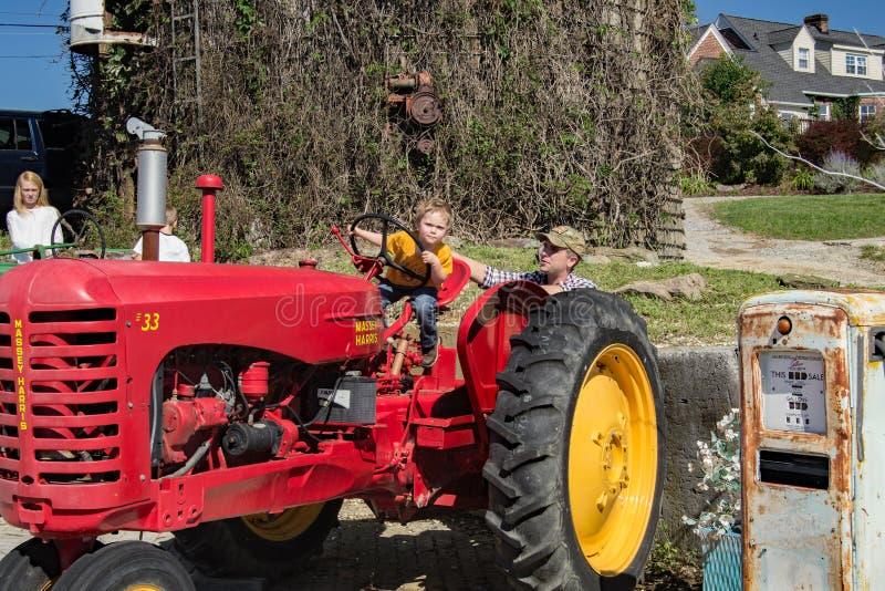 一台大红色拖拉机的一个年轻男孩 库存图片