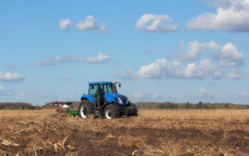 一台大蓝色拖拉机,犁领域反对美丽的天空 免版税图库摄影