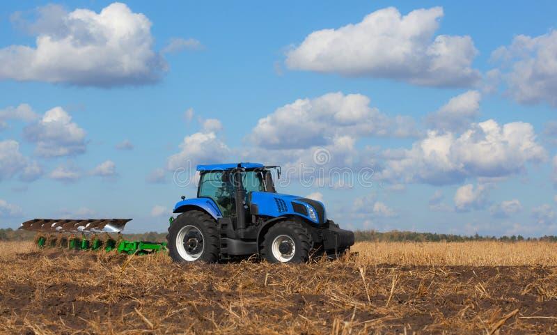 一台大蓝色拖拉机,犁领域反对美丽的天空 免版税库存照片