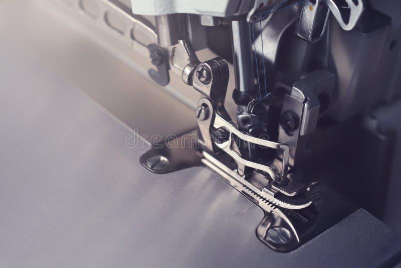 一台工业overlock缝纫机的复杂机制专业使用的在一种黑暗的被定调子的轻的心情 库存照片