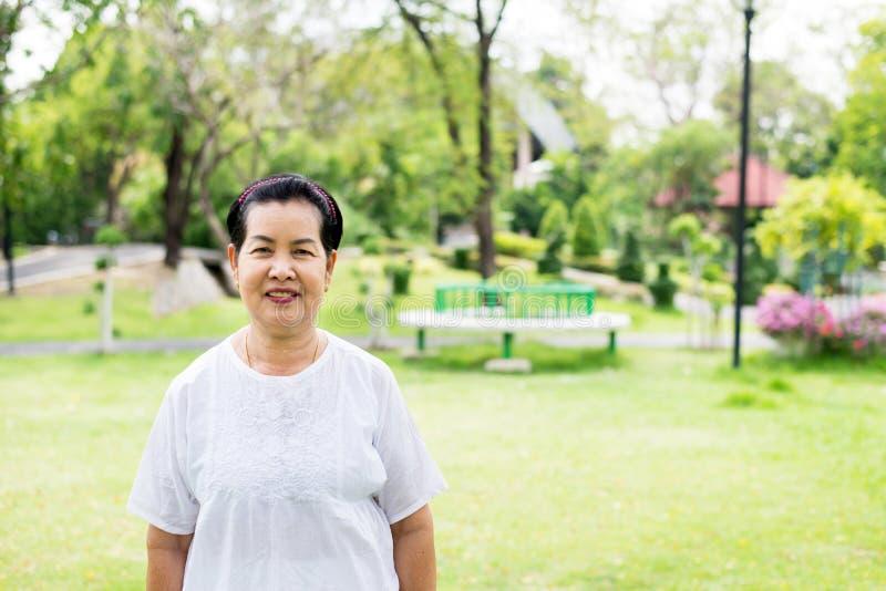 一台年长亚洲妇女身分和注视着照相机的画象公园,愉快和微笑 免版税库存照片