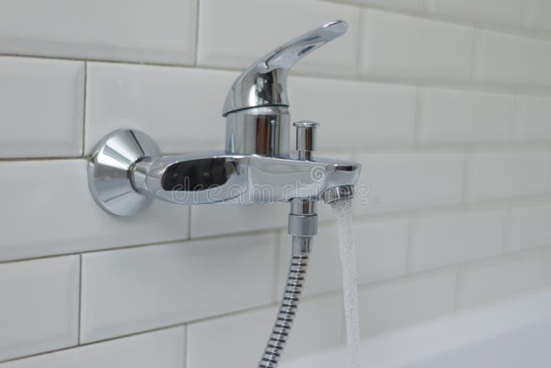 一台开放镀铬物龙头搅拌器的特写镜头在浴缸的有自来水的 库存图片