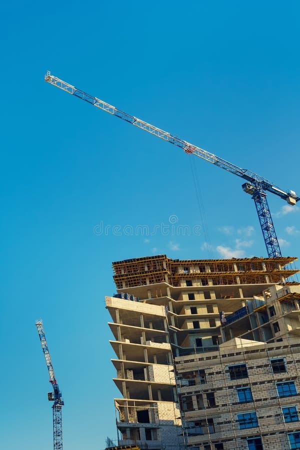 一台新的混凝土建筑和卷扬起重机的结构 免版税库存照片