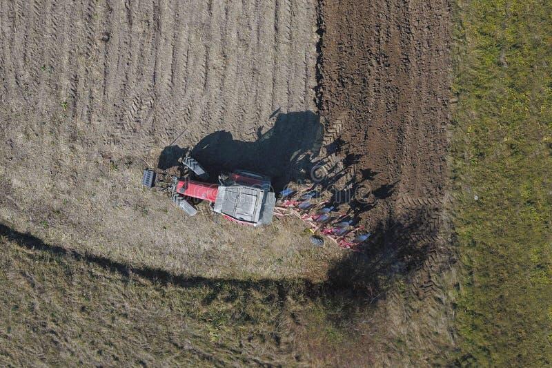 一台红色拖拉机的一位农夫有播种机的在一个私有领域的被犁的土地播种五谷在村庄区域 春天的机械化 库存照片