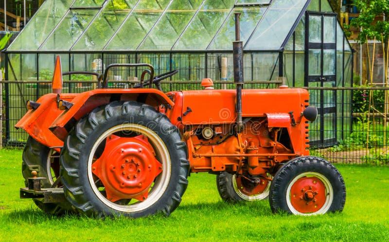 一台红色拖拉机的特写镜头在谷仓、农业运输和设备,农业机械的 库存照片