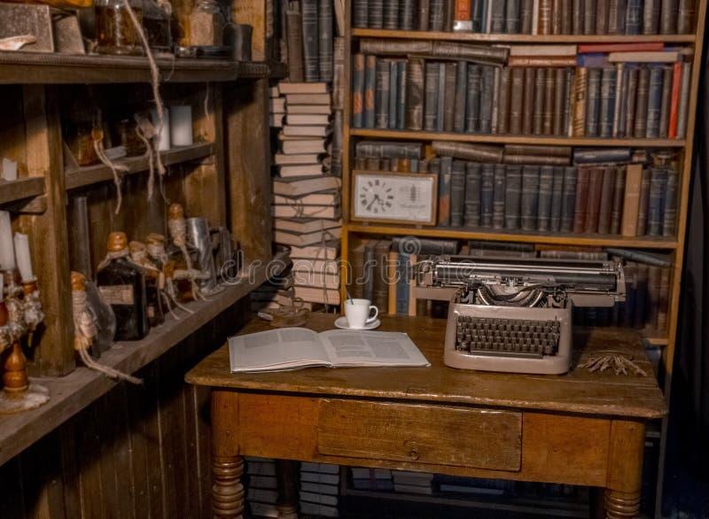 一台老打字机在桌上 作家` s室 旧书在架子 研究员的葡萄酒室,评论家,科学家, 免版税库存照片