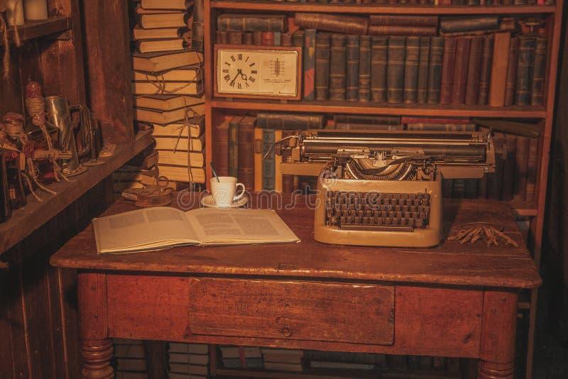 一台老打字机在桌上 作家` s室 旧书在架子 研究员的葡萄酒室,评论家,科学家, 图库摄影