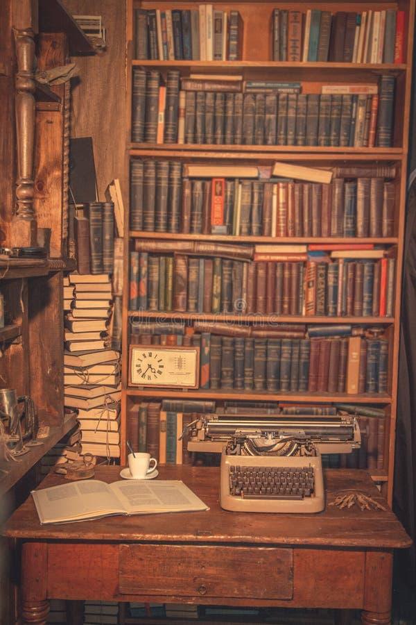 一台老打字机在桌上 作家` s室 旧书在架子 研究员的葡萄酒室,评论家,科学家, 库存照片