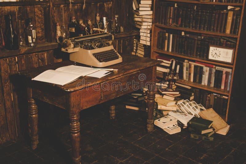 一台老打字机在桌上 作家` s室 旧书在架子 研究员的葡萄酒室,评论家,科学家, 免版税库存图片