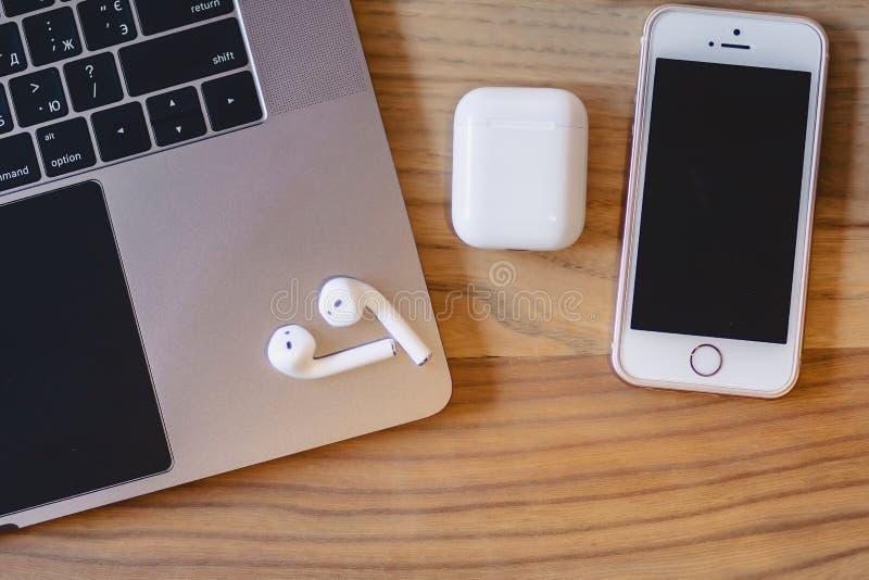 一台膝上型计算机、一个电话和一个无线耳机在一张木桌上 库存照片