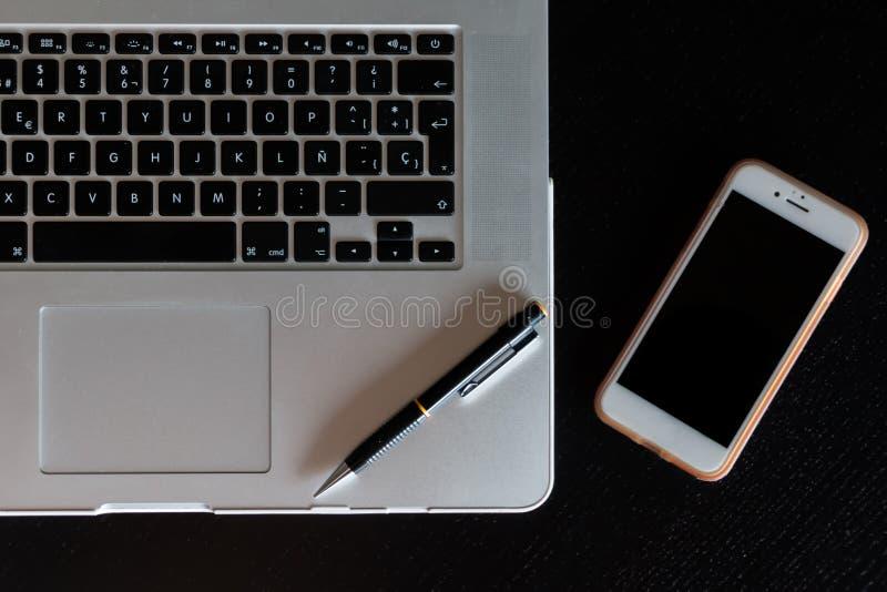 一台膝上型计算机的一个银色键盘的部份看法有一个智能手机和一支铅笔的在一张黑暗的木书桌上 免版税图库摄影