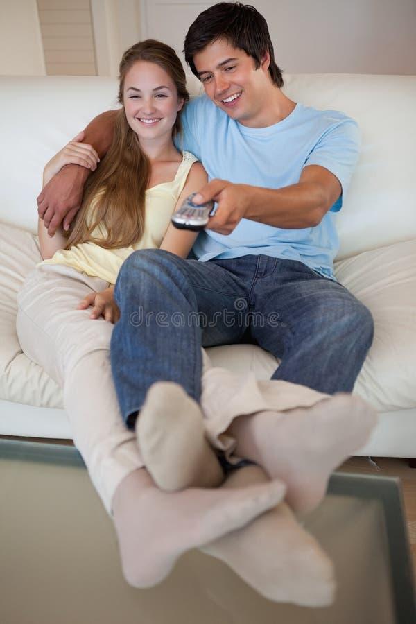 一台轻松的夫妇注意的电视的纵向 免版税图库摄影