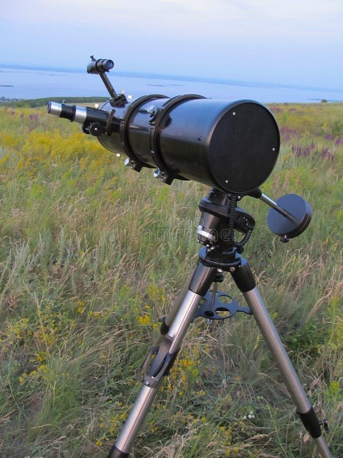 一台黑复杂望远镜在草甸站立在黄昏 库存图片