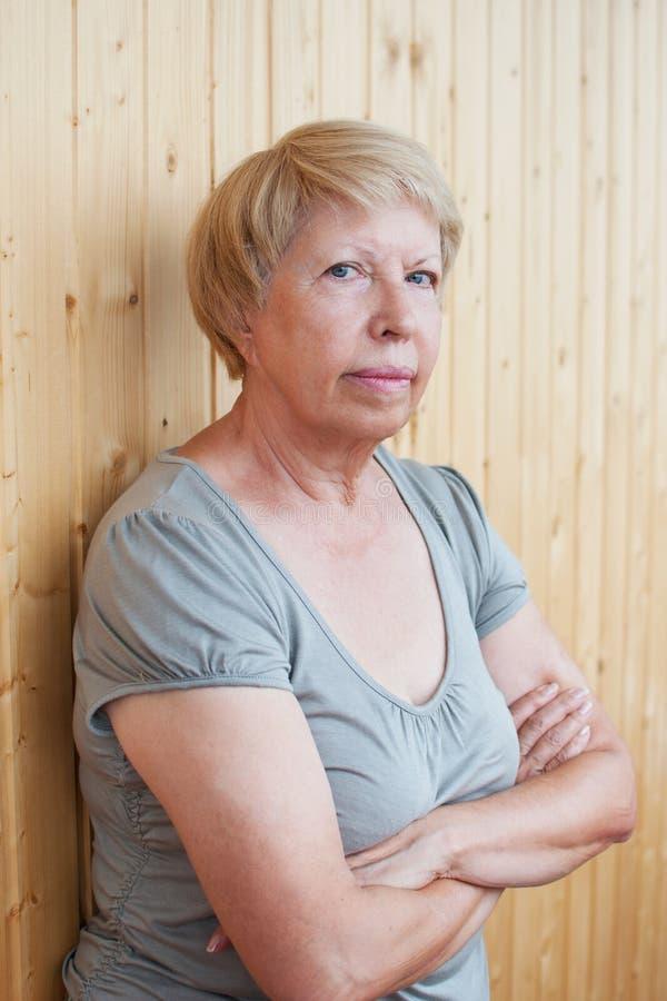 一名严肃的中年妇女的画象背景的求爱 免版税库存照片