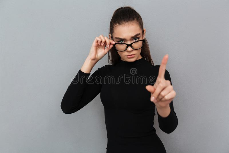 一名严肃的可爱的妇女的画象黑礼服的 图库摄影