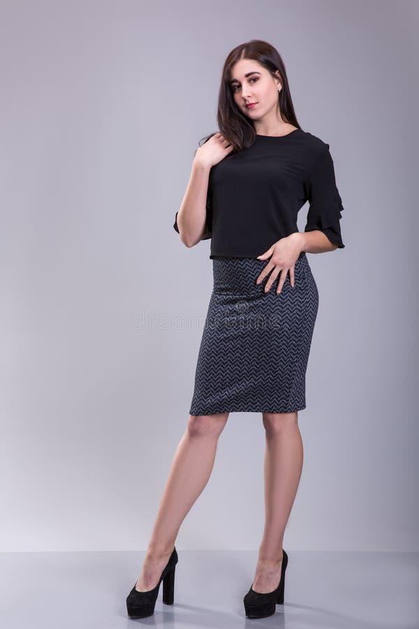 一名严肃的时髦妇女的全长画象站立在灰色背景的黑礼服的 免版税库存照片