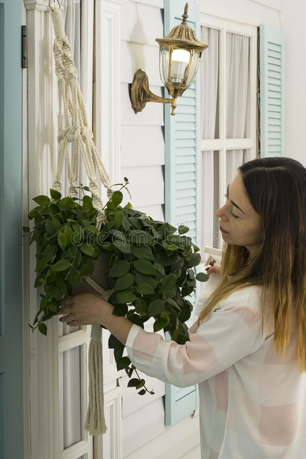 一名中年妇女在家照看在游廊的一朵花 免版税图库摄影