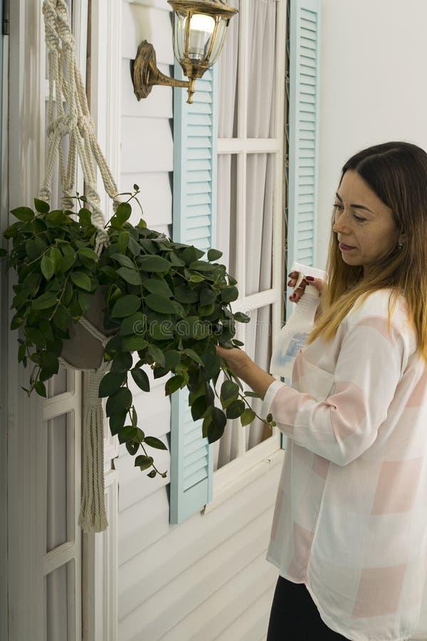 一名中年妇女在家照看在游廊的一朵花 免版税库存照片