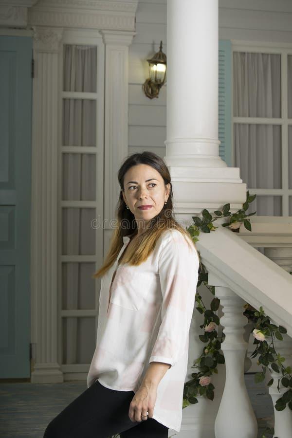 一名中年妇女在门廊站立一美丽hous 免版税库存图片