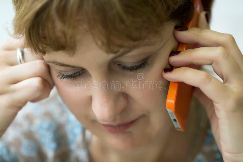 一名中年妇女的画象谈话在电话 免版税库存图片
